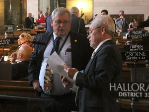 <a href='http://news.legislature.ne.gov/dist33' target='_blank' title='Link to the website of Sen. Steve Halloran'>Sen. Steve Halloran</a> (right) discusses a bill with Sen. Steve Erdman.