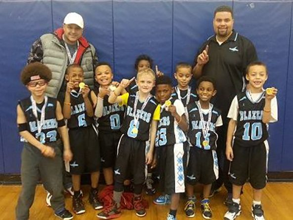 Coach Justin Wayne poses with his third grade team to celebrate winning first place in a 2014 tournament.